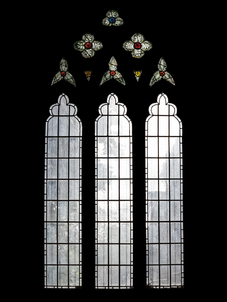 Fire-damaged CE Kempe stained glass in the north transept, 1892. Kempe and Tombleson trademarks remain in the tracery at the top.