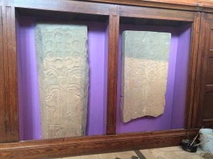 Mediaeval coffin lids, mounted inside new display cabinets, made from the existing baptistry cupboards