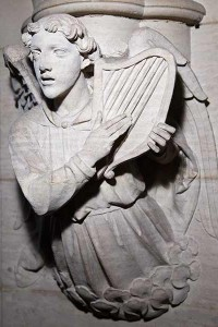 Close up of stone carving of an angel playing a harp