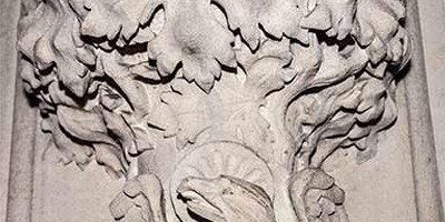 Close up of a stone carving representing St John