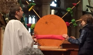 James and George making a large Christingle at the front of church